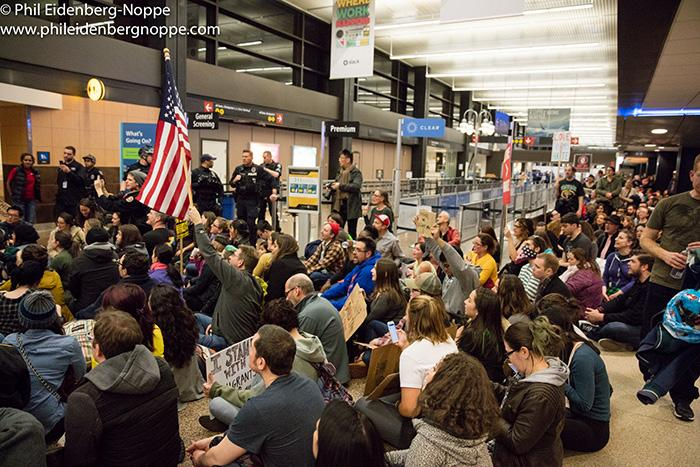 Protesters sit on the floor of the Seattle-Tacoma Airport