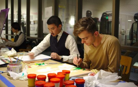 EdCC alumni Travers Cao (left) and Nazar Patriy (right) focused on their work during a live painting demonstration at the Between the Lines 2018 commencement.